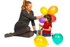 愉快的使用与气球的妈妈和女孩 免版税库存照片