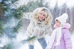 愉快的使用与雪的父母和孩子在冬天 图库摄影