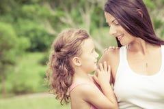 愉快的使用在公园的母亲和女儿在天时间 免版税库存图片