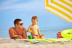 愉快的使用在海滩的父亲和孩子 免版税库存照片