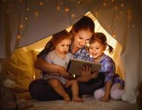 愉快的使用在片剂个人计算机的家庭母亲和孩子 库存照片