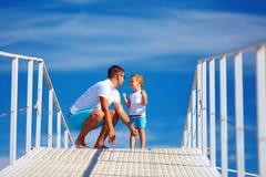 愉快的使用在蓝天天际的父亲和儿子 免版税库存照片