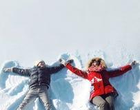 愉快的使用母亲和的儿子获得一起说谎的乐趣在雪冬天 免版税库存图片