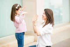 愉快的使用用手的母亲和女儿 图库摄影