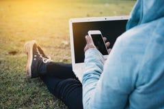 愉快的使用计算机和智能手机的行家老妇人在公园在度假放松时间 免版税库存图片