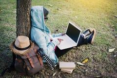 愉快的使用计算机的行家老妇人在公园在度假放松时间 库存照片