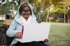 愉快的使用计算机的行家老妇人在公园在度假放松时间 库存图片