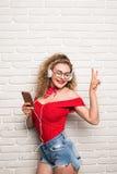 愉快的俏丽的女孩或逗人喜爱的美丽的妇女女性模型听 免版税库存图片