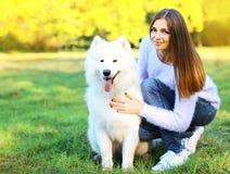 愉快的俏丽的妇女所有者和狗户外 免版税库存照片