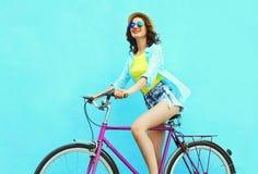 愉快的俏丽的微笑的妇女骑在五颜六色的蓝色背景的一辆自行车 免版税库存照片