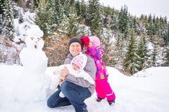 愉快的修造一个雪人的父亲和他的两个女儿在冬日 使用在与森林的自然的家庭在背景中 库存照片