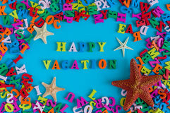 愉快的假期-词组成由小色的信件 暑假纪念品-从热带含沙海洋的海星 免版税库存图片