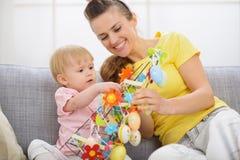 愉快的做复活节装饰的母亲和婴孩 免版税库存图片