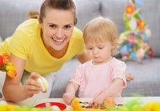 愉快的做复活节装饰的母亲和婴孩 免版税库存照片