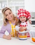 愉快的做新鲜的橙汁的妇女和子项 免版税库存图片