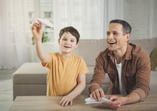 愉快的做纸航空器的爸爸和儿子 免版税库存图片