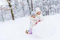 愉快的做雪人的母亲和逗人喜爱的矮小的女儿 库存照片
