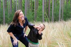 愉快的做面孔的母亲和儿子 免版税图库摄影