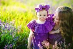 愉快的健康家庭观念 有她的走在a的麦子金领域的小逗人喜爱的女儿的一名年轻美丽的妇女 免版税库存照片