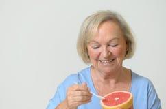 愉快的健康资深夫人用一个红色葡萄柚 免版税库存照片