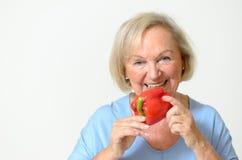 愉快的健康资深夫人用一个红辣椒 库存照片
