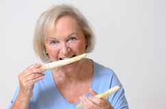 愉快的健康资深夫人用白色芦笋 免版税库存照片