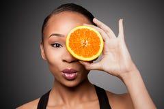 愉快的健康黑人亚裔妇女用橙色果子 免版税库存照片