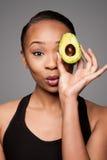 愉快的健康黑人亚裔妇女用鲕梨果子 库存照片