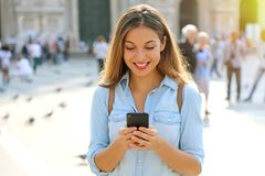 愉快的偶然发短信在聪明的电话步行的妇女佩带的衬衣 库存照片