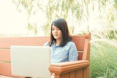 愉快的偶然美丽的妇女观看的录影或享受在坐在咖啡店大阳台的膝上型计算机的娱乐内容 库存照片