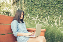 愉快的偶然美丽的妇女观看的录影或享受在坐在咖啡店的膝上型计算机的娱乐内容 图库摄影