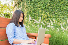 愉快的偶然美丽的妇女观看的录影或享受在坐在咖啡店的膝上型计算机的娱乐内容 免版税库存图片