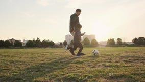 愉快的儿子和爸爸奔跑接近的看法在戏剧领域的和逐个踢足球慢动作 股票录像