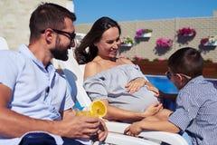 愉快的儿子接触怀孕的母亲` s腹部,当一起时休息 免版税库存图片