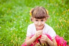 愉快的儿童嗅到的野花 免版税库存照片