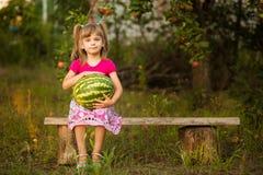 愉快的儿童女孩举行非常大西瓜在晴天 健康的概念 免版税库存照片