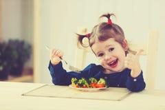 愉快的儿童女孩吃菜和显示赞许 免版税图库摄影