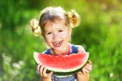 愉快的儿童女孩吃西瓜 免版税库存图片