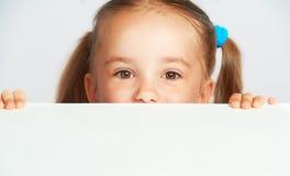 愉快的儿童女孩和空白的白色海报广告牌 库存图片