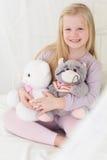 愉快的儿童女孩在与她软的玩具的床上 免版税库存照片