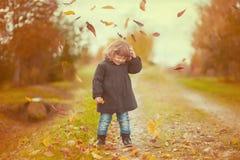 愉快的儿童女孩在公园投掷秋叶和笑 免版税库存图片