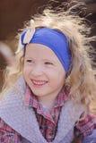 愉快的儿童女孩室外画象蓝色头饰带的和格子花呢披肩穿戴 免版税库存照片