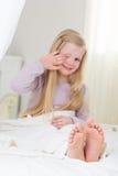 愉快的儿童女孩是坐和打呵欠在床上 免版税库存图片