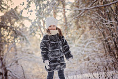 愉快的儿童女孩获得乐趣在冬天多雪的森林 免版税库存照片