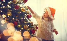 愉快的儿童女孩装饰了圣诞树 免版税库存图片