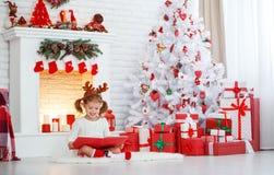 愉快的儿童女孩阅读书在圣诞树的早晨 库存图片