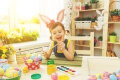愉快的儿童女孩绘复活节的鸡蛋 图库摄影