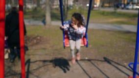 愉快的儿童摇摆的户外 逗人喜爱的女孩获得乐趣,上上下下摇摆在公园,无忧无虑的童年 股票录像