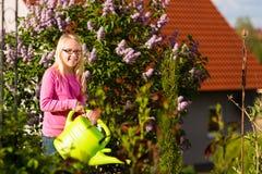 愉快的儿童浇灌的花在庭院里 免版税库存图片