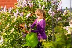 愉快的儿童浇灌的花在庭院里 免版税图库摄影